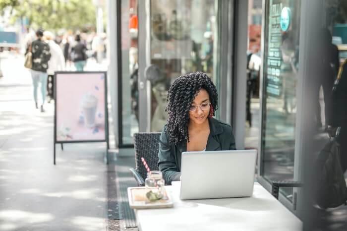 Moça mexe em seu computador sentada em mesa ao ar livre