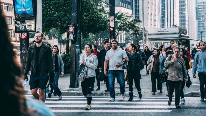 Diversas pessoas atravessando uma rua travessa da Avenida Paulista