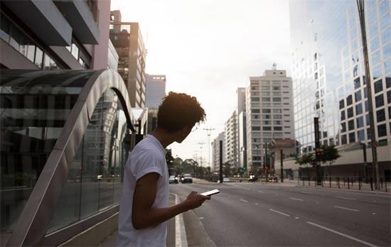 Rapaz com celular na mão observa a Avenida Paulista ao lado de estação do metrô.