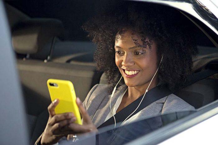 Moça sorri ao mexer em seu celular no banco de trás de um carro